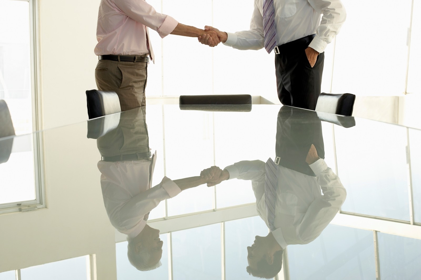 Businessmen shaking hands over a contract deal in a boardroom